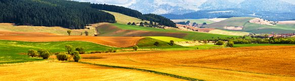 Spring tillage on hills panorama. Picturesque ploughland. In a valley in Tatras mountains of Slovakia. Rural scene of cultivated land Stock Photo