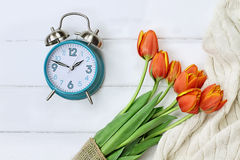 Spring Time Change Daylight Savings. Alarm clock with a beautiful bouquet of tulips and a cozy blanket shot from above in a flatlay style over a wood table top royalty free stock photo