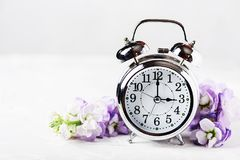 Spring Time Change. Spring flowers and Alarm Clock Stock Images