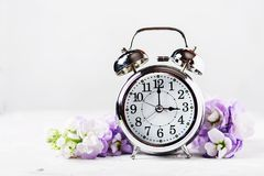 Spring Time Change. Spring flowers and Alarm Clock Stock Photography