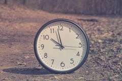 Spring Time Change. Summer back concept. Vintage alarm Clock outdoors stock photography