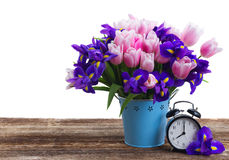 Spring time concept. Retro alarm clock with bouquet of flowers over white background Stock Image