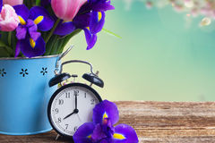 Spring time concept. Retro alarm clock with flowers copy space on blue bokeh background Stock Image