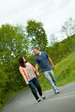 Spring Time Couple. Young happy couple enjoying each others company outdoors walking down an empty road. A very fitting theme for the start of marriage or any royalty free stock photo