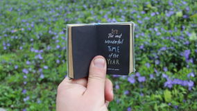 Spring time idea. Book with text and spring field with blue flowers. stock footage