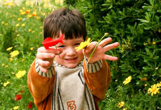 Spring time. Little boy  playing in the green fields ,enjoy  the spring time ,  shows to us the flowers that he is holding Royalty Free Stock Images