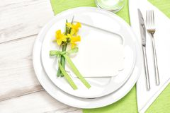 Spring table decoration narcissus flowers White plate fork knife Stock Photos