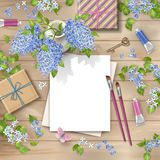 Spring Top View Background. Spring top view wooden background blossoming tree branches in a ceramic vase, blank piece of paper, gifts, paints and brushes Royalty Free Stock Photo
