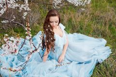 Spring touch. Happy beautiful young smiling woman in blue dress enjoy fresh flowers and sun light in blossom park at. Sunset Royalty Free Stock Image