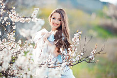 Spring touch. Happy beautiful young smiling woman in blue dress enjoy fresh flowers and sun light in blossom park at. Sunset Stock Photo