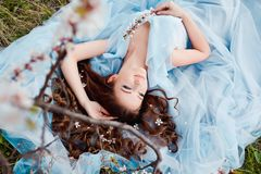 Spring touch. Happy beautiful young smiling woman in blue dress enjoy fresh flowers and sun light in blossom park at. Sunset Royalty Free Stock Photos