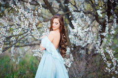 Spring touch. Happy beautiful young woman in blue dress enjoy fresh flowers and sun light in blossom park at sunset Royalty Free Stock Photography