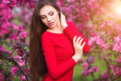 Spring touch. Happy beautiful young woman in red dress enjoy fresh pink flowers and sun light in blossom park at sunset. Stock Photos