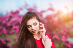 Spring touch. Happy beautiful young woman in red dress enjoy fresh pink flowers and sun light in blossom park at sunset. Stock Photography