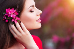 Spring touch. Happy beautiful young woman in red dress enjoy fresh pink flowers and sun light in blossom park at sunset. Royalty Free Stock Image