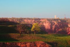 A Spring Tree and the ground collapse. A lonely tree on the hills at the evening light. Ground collapse spring landscape, Kriviy Rih, Ukraine royalty free stock images