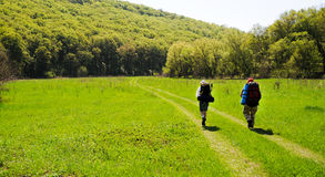Spring trekking. Two hikers going on a spring meadow. Day is sunny and warm. Grass is brilliant green. Hills covered with forest Stock Photos