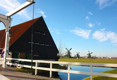 Spring trip to Zaanse Schans. Placid channels, tranquil rivers flow between the hills. The Dutch windmills stand as a traditional. Tourist landmark after royalty free stock images
