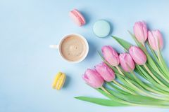 Spring tulip flowers, colorful macaroons and coffee on blue pastel table top view. Beautiful breakfast on Mothers or Womans day. Flat lay Stock Photos
