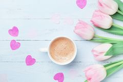 Spring tulip flowers and cup of coffee on pastel blue table top view. Beautiful spring breakfast on Mothers or Womans day.Flat lay stock photos