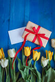Spring tulip flowers, gift box and paper card on blue wooden table from above in flat lay style. Royalty Free Stock Image