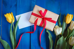 Spring tulip flowers, gift box and paper card on blue wooden table from above in flat lay style. Stock Images