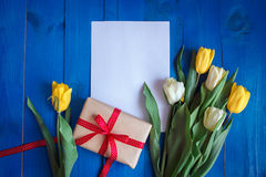 Spring tulip flowers, gift box and paper card on blue wooden table from above in flat lay style. Royalty Free Stock Photography