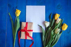 Spring tulip flowers, gift box and paper card on blue wooden table from above in flat lay style. Stock Photos