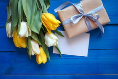 Spring tulip flowers, gift box and paper card on blue wooden table from above in flat lay style. Royalty Free Stock Images