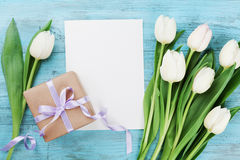 Spring tulip flowers, gift box and paper card on turquoise vintage table from above in flat lay style. Greeting for Mothers Day. Stock Photography