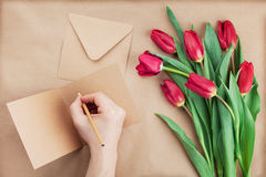 Spring tulip flowers and man hand signing a card on brown background top view flat lay style. Greeting for Birthday or Womans day. Royalty Free Stock Image