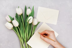 Spring tulip flowers and man hand signing a card on gray stone table top view in flat lay style. Greeting for Womens or Mothers Da Stock Photos
