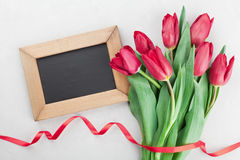 Spring tulip flowers with ribbon and wooden frame with empty space for text on gray stone table top view in flat lay style. Royalty Free Stock Images