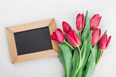 Spring tulip flowers and wooden frame with empty space for text on gray stone table top view in flat lay style. Stock Photography