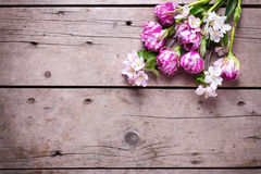 Spring tulips and apple tree flowers on aged wooden  background Stock Photo