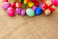 Spring tulips with colorful easter eggs and gift box. Royalty Free Stock Images