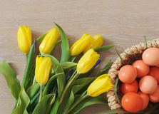 Spring tulips and Easter eggs lying on wood Stock Photo