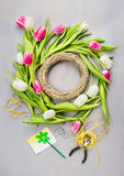 Spring tulips flowers wreath making on gray background Royalty Free Stock Photos