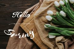 Spring tulips on tablecloth and wooden board with hello spring lettering. Top view of spring tulips on tablecloth and wooden board with hello spring lettering Stock Image