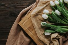 Spring tulips on tablecloth and wooden board for international womens day. Top view of spring tulips on tablecloth and wooden board for international womens day Royalty Free Stock Photo