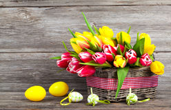 Spring tulips in wooden basket with Easter eggs Stock Image