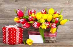 Spring tulips in wooden basket, red polka-dot gift box. Happy mothers day, romantic still life, fresh flowers. on wooden background stock photos
