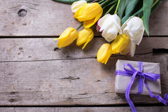 Spring tulips and wrapped  box  on vintage wooden background. Royalty Free Stock Images