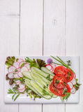 Spring vegan salad with tomato, cucumbers, radish on a white plate. Top view. Royalty Free Stock Photography