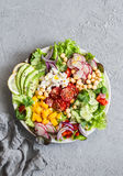 Spring vegetable buddha bowl. Salad with veggies, chickpeas, avocado and feta. Delicious healthy food.  On a gray background Royalty Free Stock Images