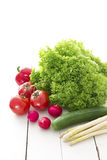 Spring vegetables. And greens on white wooden table royalty free stock photography