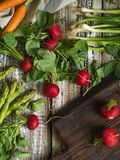Spring vegetables - carrots, radishes, asparagus, green onions on an old wooden background. Royalty Free Stock Image