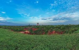 Spring view on the ground collapse. Ukrainian mine activity landscape at the Springtime. Spring green cloudy landscape. Ground collapse landscape. Technogenic royalty free stock image