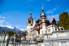 Spring view of Peles Castle with snowy Bucegi Mountains in the background. Royalty Free Stock Images