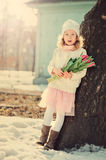 Spring vintage tones portrait of child girl with tulips bouquet for woman's day Royalty Free Stock Photo